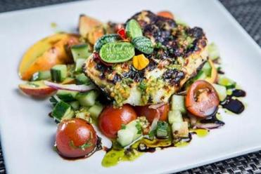 Halloumi cheese comes off the grill smoky and chewy, on a plate with cherry tomatoes, peaches, and pepper.